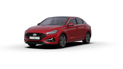 Front side view of the new Hyundai i30 Fastback in the colour Sunset Red.